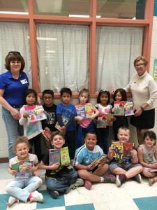 Students in Mrs. Sarah DiLuzio's kindergarten class show off their new books with Rotarians Sharon Marshall, back left and Cathy Cardaneo, back right.