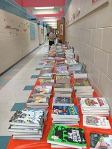 Books on display for selection by students at Long Neck Elementary during their spring Book Fair. Rotarian Cathy Cardaneo stands in rear, ready to assist.