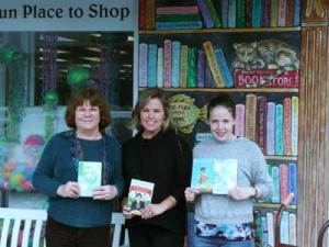 4th and 5th grade book titles are shown off by Rotarians Sharon Marshall (left), Tracey Gross (center) and Alex Colvedos, Browseabout Books (right).