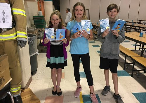 8th Grade students holding their new books