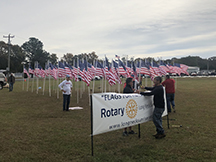 Rotarians setting up the club banner before the flag display