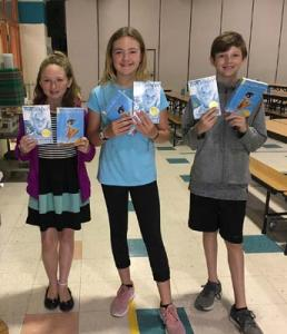 Long Neck Elementary School 5th graders (left to right) Makenzie Story, Ellen Kline and Joseph Sekcienski display the two novels provided to  all students in the 5th grade: Esperanza Rising and Number the Stars.