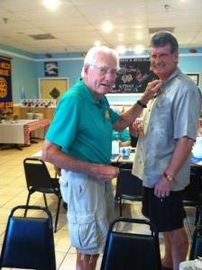 Rotarian Fred Gibbs pins new member  Walt Ellendale